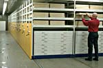 Photograph of the mobile shelving units used to store the �pizza boxes� used for oversize paper documents.