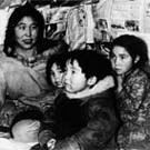 Photograph of Arnakallak's family, in their home. From left to right: Qaumajuq, Piipi Nasaq, Jonathan, Rhoda and Arnakallak, Pond Inlet (Mittimatalik/Tununiq), Nunavut, circa 1940-1944