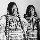 Portrait of three Inuit women wearing beaded baby-pouches. This photograph was taken in a studio at Fullerton, Nunavut, 1904