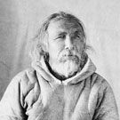 Photographic portrait of Mallikee wearing a skin parka and fur mittens; this photograph was taken in a studio and then placed in an oval frame. Fullerton, Nunavut, 1904-1905