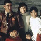 Photograph of a group of Inuit consisting of a man, women and children on the deck of an Eastern Arctic expedition ship, unknown location, Nunavut, 1958