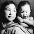 Photograph of an Inuit girl carrying an infant in a baby-pouch, Taloyoak (formerly Spence Bay), Nunavut, circa 1961