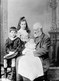 Photograph of Sir Sandford Fleming with his grandchildren: a young girl, a small boy and a baby, held in Fleming's arms