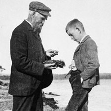 Photograph of John Macoun and a boy examining a bird's nest