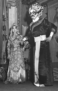 Photograph of two actors in Chinese theatrical costume on stage, with musicans seated at side of stage