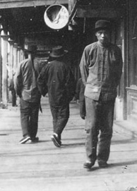 Photograph of man walking toward camera in front of stores, on wooden sidewalk covered by balcony