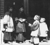 Photograph of four children wearing traditional Chinese clothing, standing in brick storefront doorway