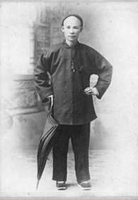 Photograph of man wearing traditional Chinese clothes, standing with umbrella