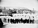 Photograph of an outdoor hockey game with spectators lining the rink, 1884