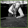 Man guides automatic cloth cutter through numerous layers of khaki cloth in pattern of chalk-outlined Canadian army uniform