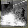 Workmen tapping molten steel from ladle into ingot forms at Sorel Steel plant
