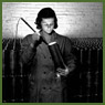 Female munitions worker uses light to inspect interior of 25-pounder field gun case at a munitions plant (prob. Robert Mitchell Co.)