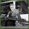 Veronica Foster, an employee of the John Inglis Co. Ltd. Bren gun plant, known as 'The Bren Gun Girl' poses with a finished Bren gun at the John Inglis Co. plant