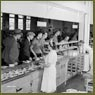 Women cafeteria workers serve male workers at the Cherrier bomb-making plant