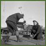 Female shipyard worker swings a heavy hammer to drive a rivet into place while another female shipyard worker holds the rivet in place during construction of a ship in the Pictou shipyard
