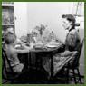 Mrs. Jack Wright and her sons Ralph and David eating breakfast at the table