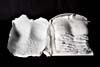 An opened book is lying flat with pages made of white plaster moulded on a woman's torso. On the left-hand page, the back of the page is white and moulded with the imprint of breasts. On the right-hand page, a moulded torso with two hands is resting on the stomach, with black handwritten text between the fingers and a black outlined picture in the mid-section of the torso.