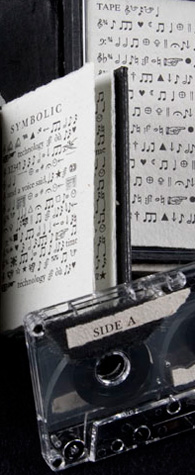 Parts of two books with white pages printed with various black symbols and musical notes, and of a labelled cassette tape.