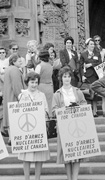 Black-and-white photograph of women protesting against nuclear arms, grouped on steps, and holding signs
