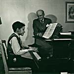 Photograph of Glenn Gould playing the piano, with his teacher Alberto Guerrero standing by, c. 1945