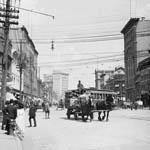 Photograph of Main Street with horse-drawn buggies, an electric street car and a number of pedestrians, Winnipeg, Manitoba, ca. 1909