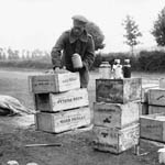Photograph of a man unpacking boxes containing jars of food, 1916