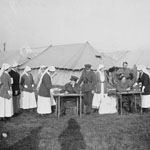 Photograph of nurses lined up at two outdoor tables to receive their ballots from four officers, while one nurse votes at a ballot box, France, 1917