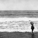 Photograph of child standing at the edge of a beach while waves roll in, near Dartmouth, Nova Scotia, date unknown