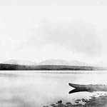 Black and white photograph of a lake with part of a canoe visible in the foreground; in the background: a shoreline covered in dense forest and a mountain range