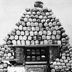 Photograph of a pyramid made from loaves of bread, built around a stove, 1897