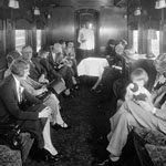 Photograph of a bright railway observation car with people sitting in comfortable seats along the windows on either side, circa 1920s