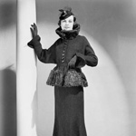 Photograph of a female model wearing a fashionable fur-trimmed suit, circa 1938