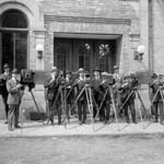 Photograph of ten men, most with cameras, outside the Canadian Motion Picture Bureau building, Ottawa, 1923