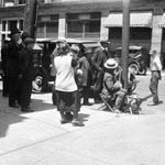 Photograph of pedestrians gathering around a street musician playing a banjo, Toronto, 1925