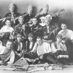 Photograph of a group of Ukrainian men and women, many holding stringed instruments, wearing traditional costumes, Edmonton, 1924