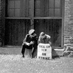 Photograph of two men, one in uniform, the other holding a picket sign, seated on a low window ledge outside a factory, possibly in Toronto, date unknown