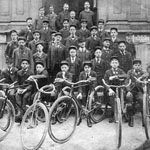Photograph of a group newspaper carriers, men and boys, with bicycles, in front of the Great North Western Telegraph Company office, Montréal, date unknown