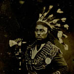 Framed photograph of an Aboriginal man in headdress and full costume, posing in a proud stance with his hand resting on an axe, circa 1846-1848