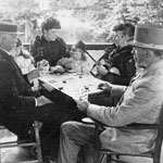 Photograph of four well-dressed adults playing cards on a verandah while two little girls look on, near Long Branch, Ontario, 1893