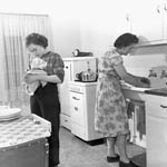 Photograph of Mrs. Bluett and daughter Margaret washing dishes their first night in new home, part of Toronto slum clearance project, circa 1949