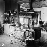 Photograph of a large kitchen with a wooden cooking stove, and a man reading a newspaper in the background, Ottawa, 1896