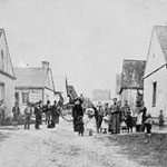 Stereograph of the village of Jeune-Lorette showing Wendat standing in a street with buildings on both sides, near Québec, Quebec, date unknown