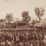 Photograph of a crowd standing before a covered wooden platform to watch campaign speeches, Longueuil, Quebec, 1858
