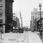 Photograph of a Calgary street showing buildings, cars, streetcars and lamposts, date unknown