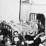 Photograph of four men lying across a bed, with three other men lying on mattresses on the floor, circa 1936