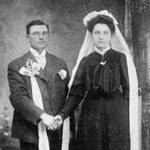 Photograph of a bride and groom wearing dark clothes, standing in a room and holding hands, 1907