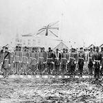 Composite photograph of a volunteer military company standing at attention on muddy and snowy ground, Victoria, British Columbia, circa 1860-1864