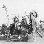 Photograph of many Aboriginal men in traditional clothing at a pow-pow, possibly Alberta, 1910