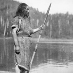 Photograph of an Aboriginal man standing on the shore with a spear, British Columbia, 1916