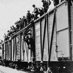 Photograph of strikers from unemployment camps getting on top of trains to go to eastern Canada, Kamloops, British Columbia, 1935